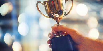 Winner hold trophy.