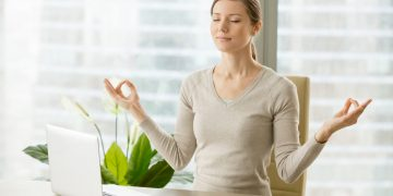 Relaxed woman meditating at workplace, practicing eastern spiritual practices for stress relief and mental health while sitting at desk in front of laptop. Short break in work for strength recovery